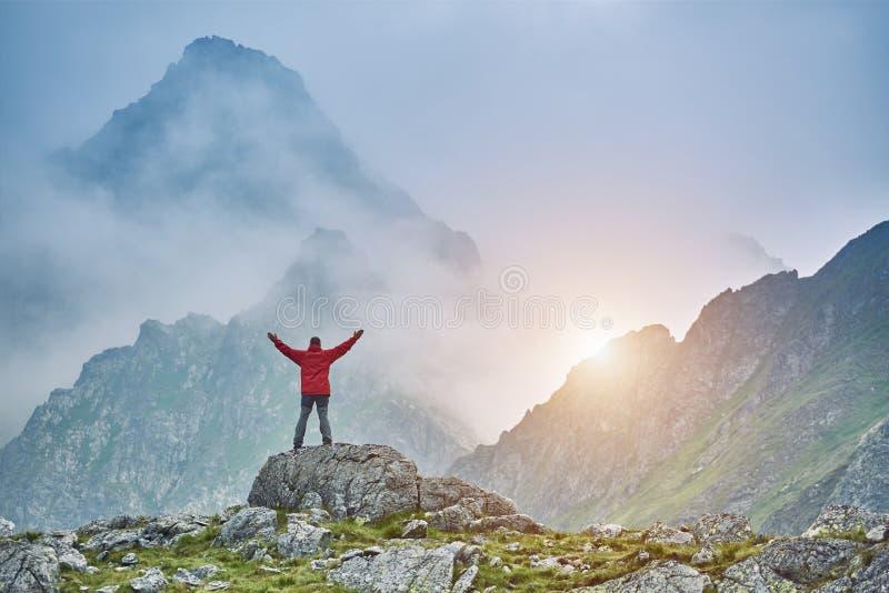 Mężczyzna na skale spotyka słońce który wzrasta od gór za, obrazy royalty free
