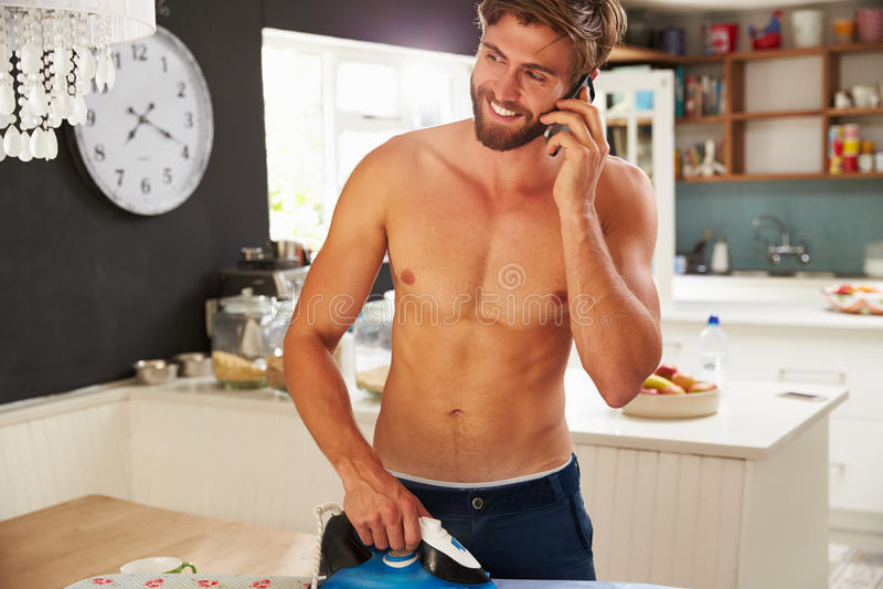 Mężczyzna Na telefon komórkowy pozyci W Kuchennej prasowanie koszula zdjęcie stock