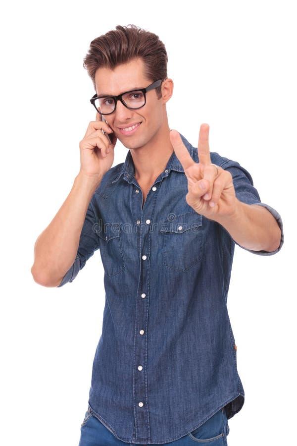 Mężczyzna na telefonie pokazuje zwycięstwo znaka fotografia royalty free