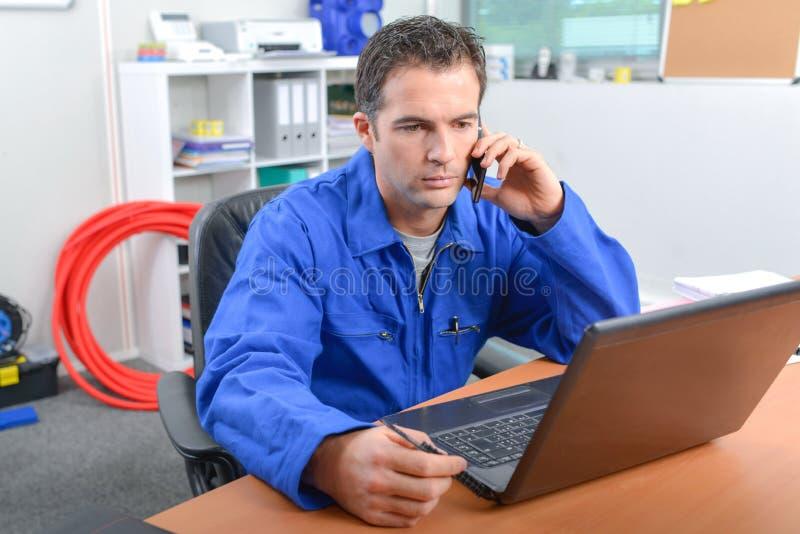 Mężczyzna na telefonie w frontowym komputerze obraz royalty free