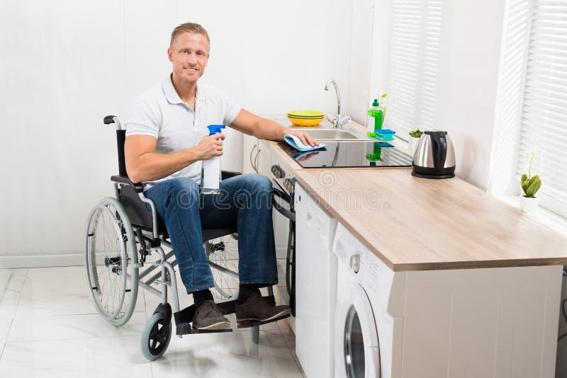 Mężczyzna na wózka inwalidzkiego cleaning indukci kuchence obraz royalty free