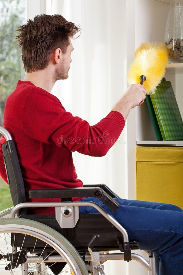 Mężczyzna na wózku inwalidzkim podczas cleaning zdjęcia stock