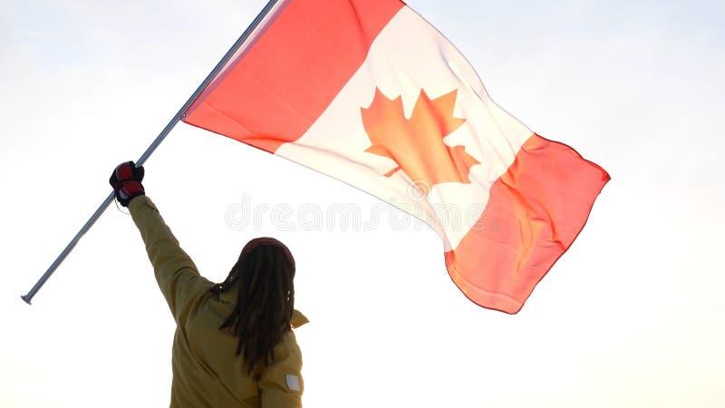 Mężczyzna na wierzchołku z kanadyjczyk flaga Zwycięzca i motywaci pojęcie obraz stock