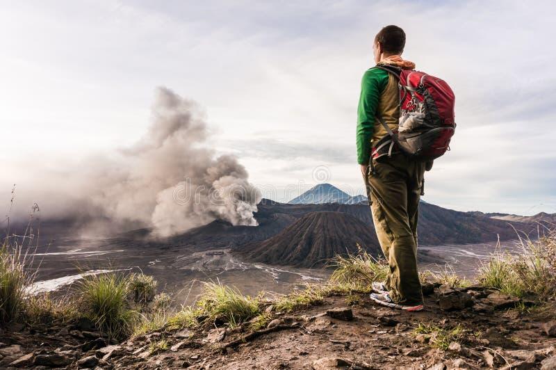 Mężczyzna na wzgórzu jest przyglądający na Bromo wulkanu erupci Bromo Tengger Semeru park narodowy fotografia stock