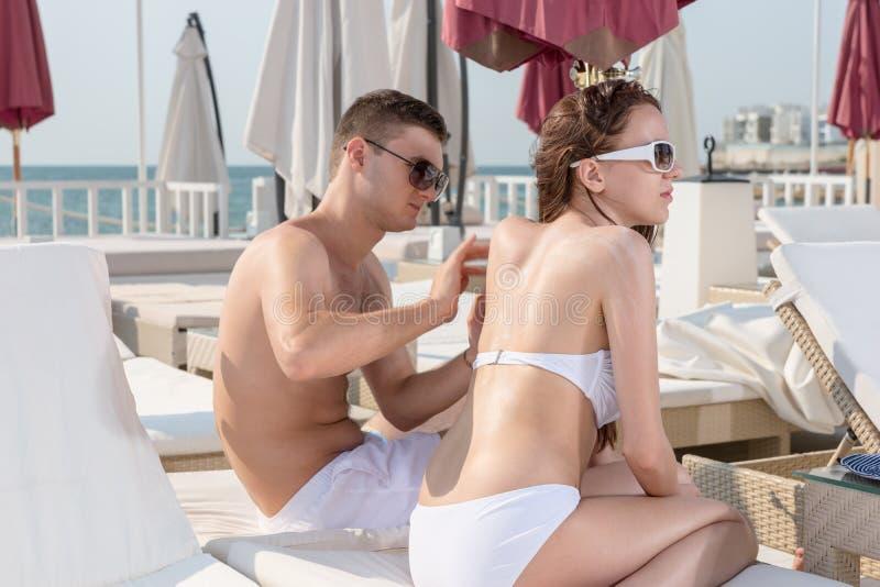 Mężczyzna nacierania płukanki kobiety plecy na Pogodnym patiu zdjęcie royalty free