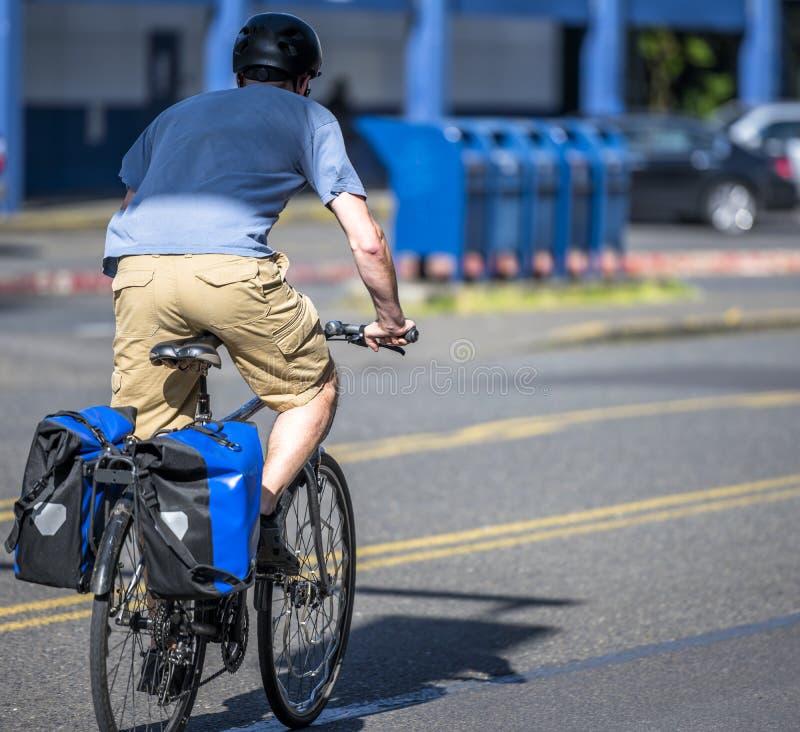 Mężczyzna naciska następy w skrótach i koszulce jedzie bicykl na miasto ulicie z wysiłkiem fotografia stock
