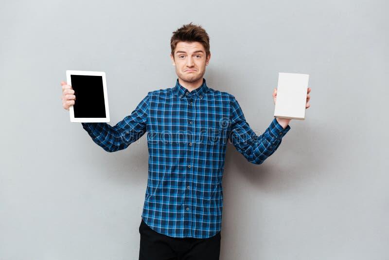 Mężczyzna nad popielatym ściennym mienie pastylki komputerem i książką obrazy royalty free