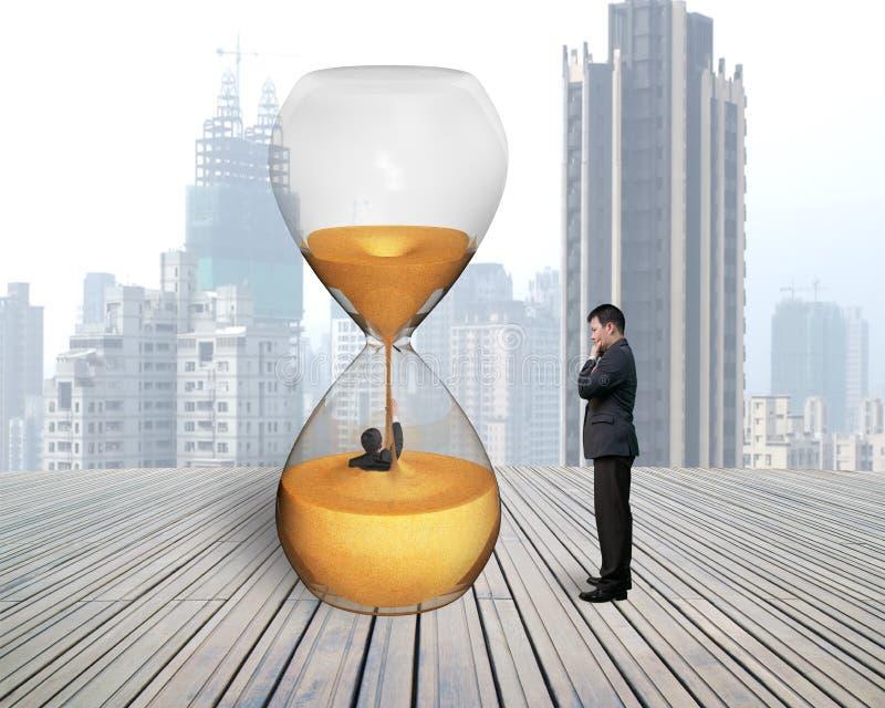 Mężczyzna nadzoruje biznesmena zalewającego w hourglass obraz stock