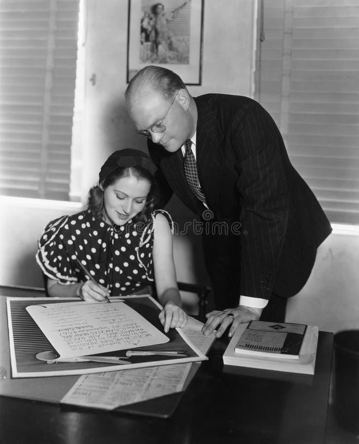 Mężczyzna nadzoruje kobiety podpisywania dokument (Wszystkie persons przedstawiający no są długiego utrzymania i żadny nieruchomo obraz royalty free