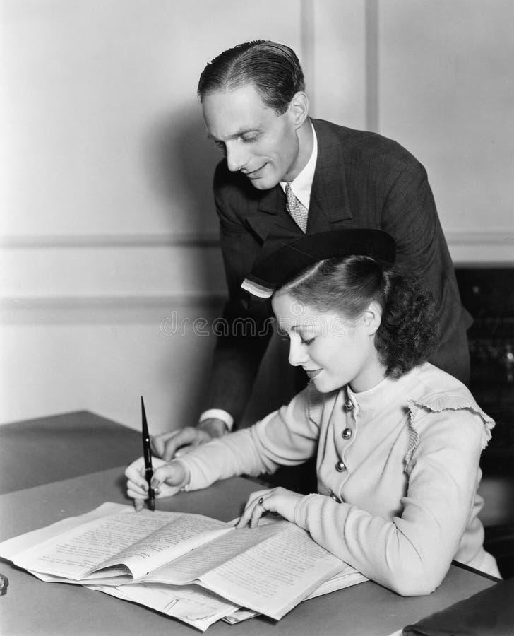 Mężczyzna nadzoruje młodej kobiety pracę (Wszystkie persons przedstawiający no są długiego utrzymania i żadny nieruchomość istnie zdjęcia stock
