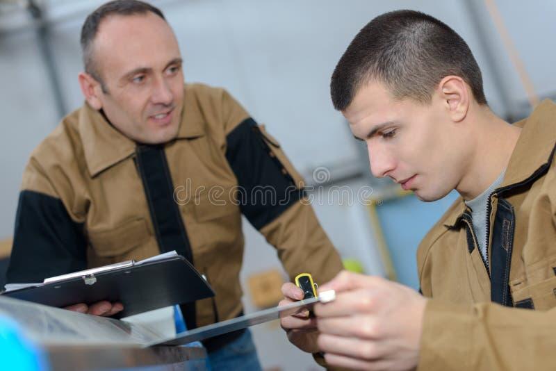 Mężczyzna nadzoruje praktykanta działanie zdjęcia royalty free