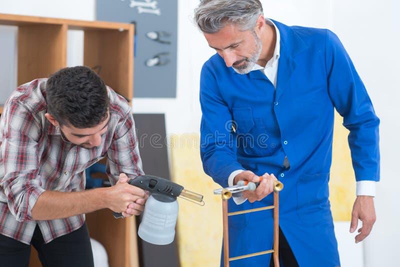 Mężczyzna nadzoruje praktykanta pracuje z blowtorch fotografia royalty free