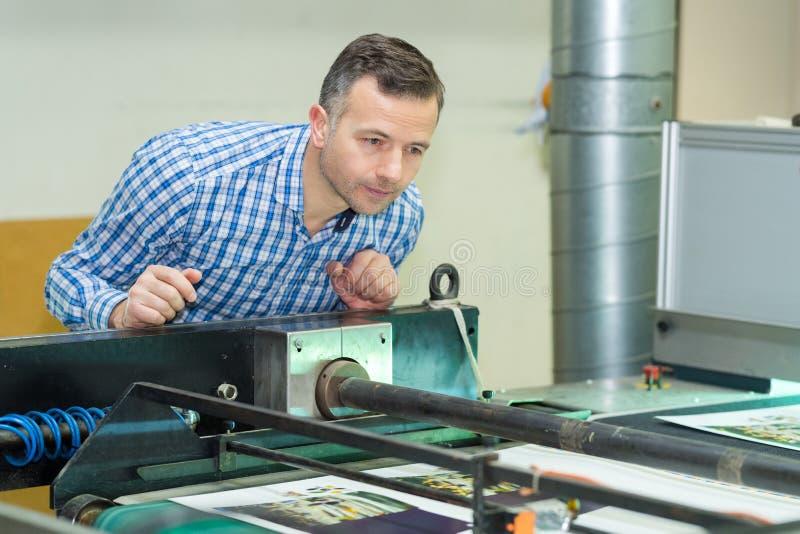 Mężczyzna nadzoruje przemysłową drukową maszynę obrazy stock