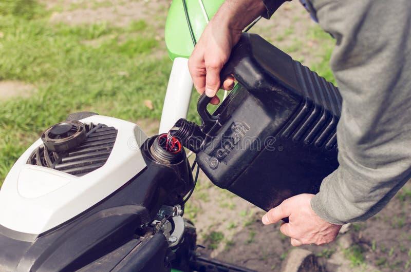Mężczyzna nalewa benzynę od kanisteru w kultywatora zbiornika zdjęcie stock
