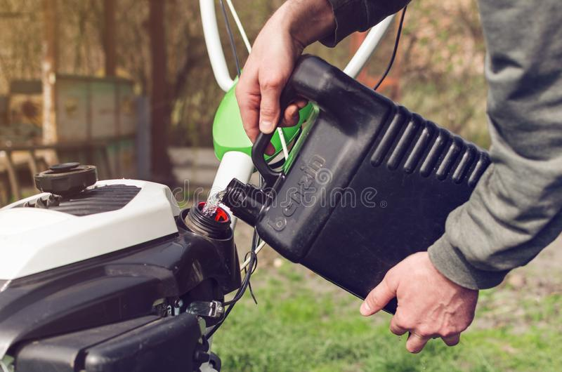 Mężczyzna nalewa benzynę od kanisteru w kultywatora zbiornika fotografia stock
