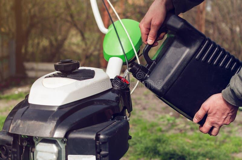 Mężczyzna nalewa benzynę od kanisteru w kultywatora zbiornika zdjęcie royalty free