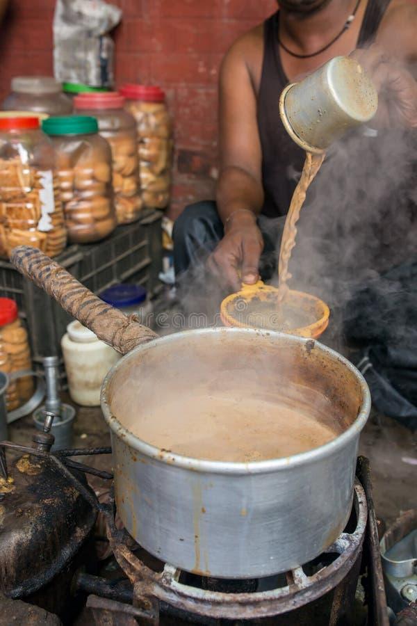 Mężczyzna nalewa filiżankę gorący herbaciany indianina styl lub Chai dla klientów w jego sklep wzdłuż ulicy w Kolkata, India obrazy stock