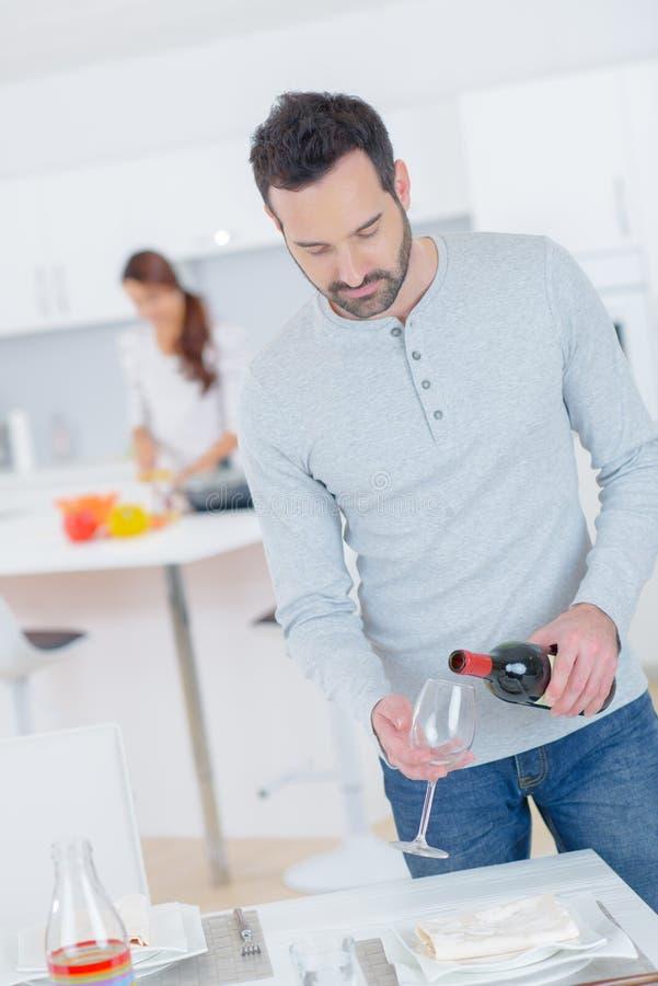 Mężczyzna nalewa szklanego wino obraz stock