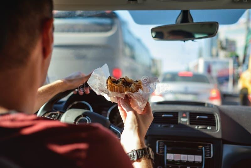 Mężczyzna napędowy samochód podczas gdy jedzący hamburger obrazy stock