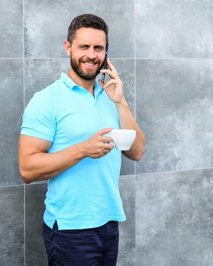 Mężczyzna napoju cappuccino mówi telefonu popielatego ściennego tło uspokój się razem Najlepszy miejsce pracy korzyści pracodawcy zdjęcie stock