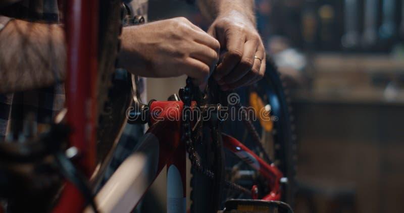 Mężczyzna naprawia bicykl w garażu obraz royalty free