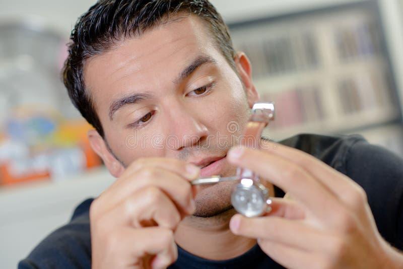 Mężczyzna naprawia jego zegarek fotografia royalty free