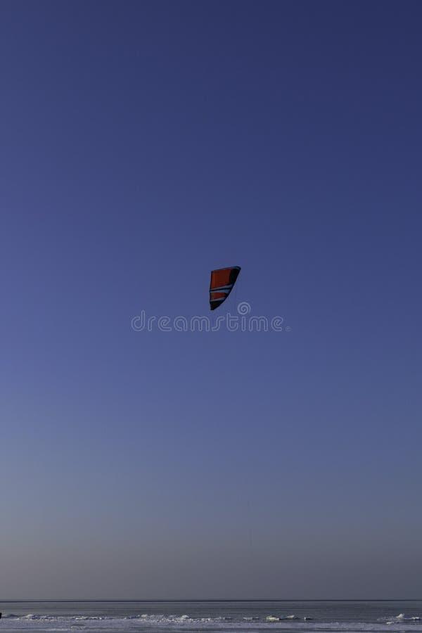 Mężczyzna narciarski kiting na zamarzniętym morzu zdjęcie stock