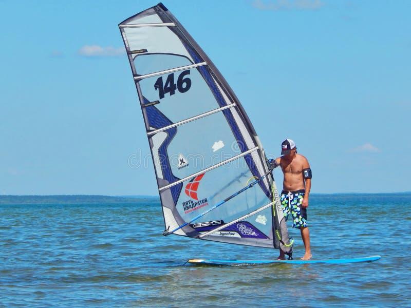 Mężczyzna narządzanie dla windsurfing na Plescheevo jeziorze blisko miasteczka Pereyaslavl-Zalessky w Rosja obraz stock
