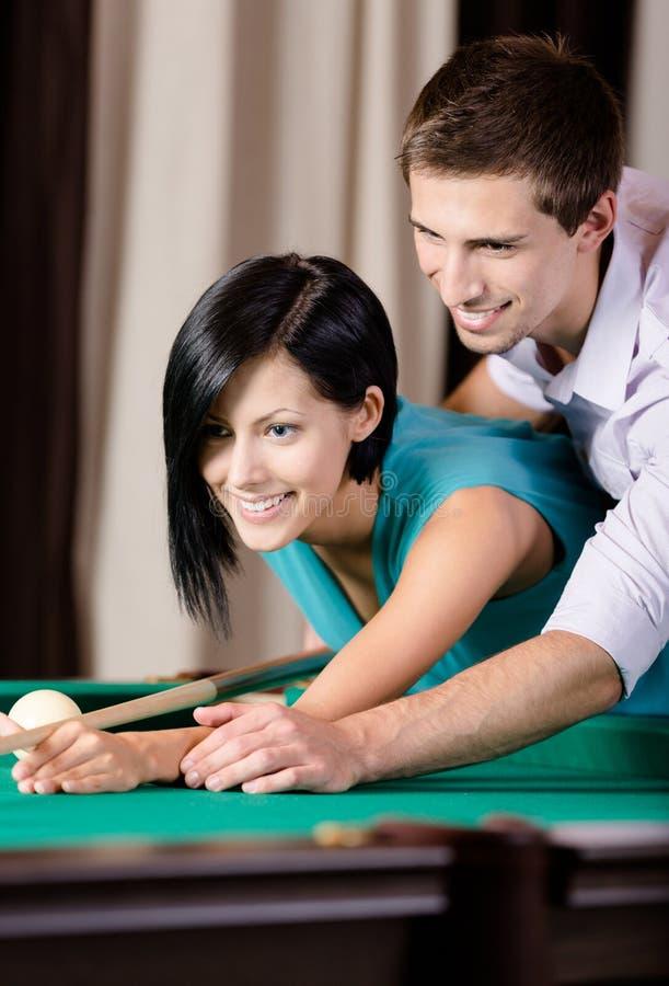 Mężczyzna nauczania młoda kobieta bawić się billiards zdjęcie royalty free