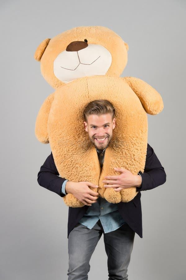 Mężczyzna niesie gigantycznego misia na szyi, popielaty tło Urodzinowego prezenta pojęcie Misia mokietu zabawki przyjemna niespod zdjęcie royalty free