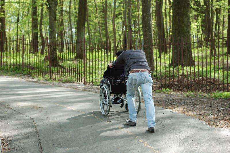 Mężczyzna niesie niepełnosprawnej osoby w wózku inwalidzkim obrazy royalty free