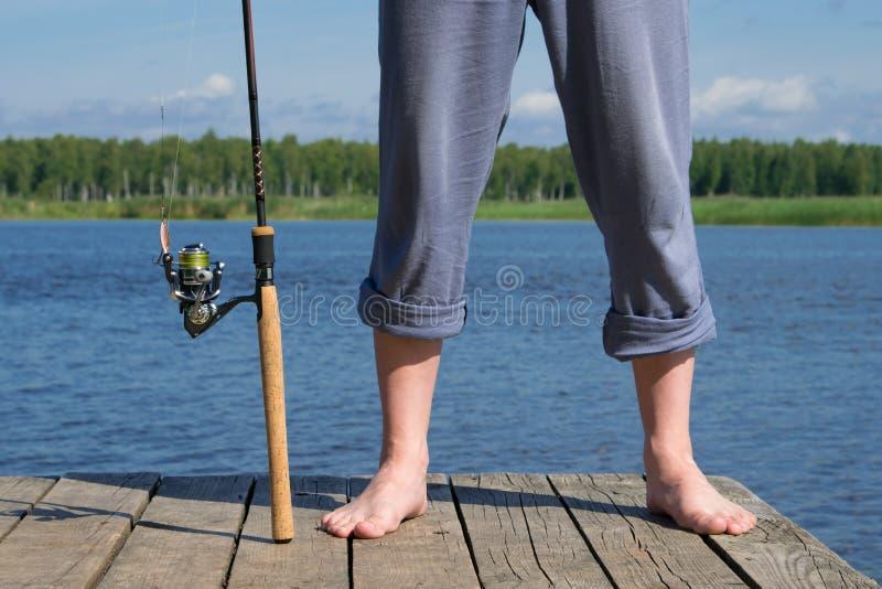 Mężczyzna nogi z połowu prąciem na molu na tle natura i woda, obraz royalty free