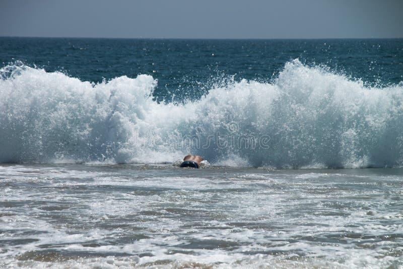 mężczyzna nurkuje pływać w ogromnej dużej fala fotografia royalty free