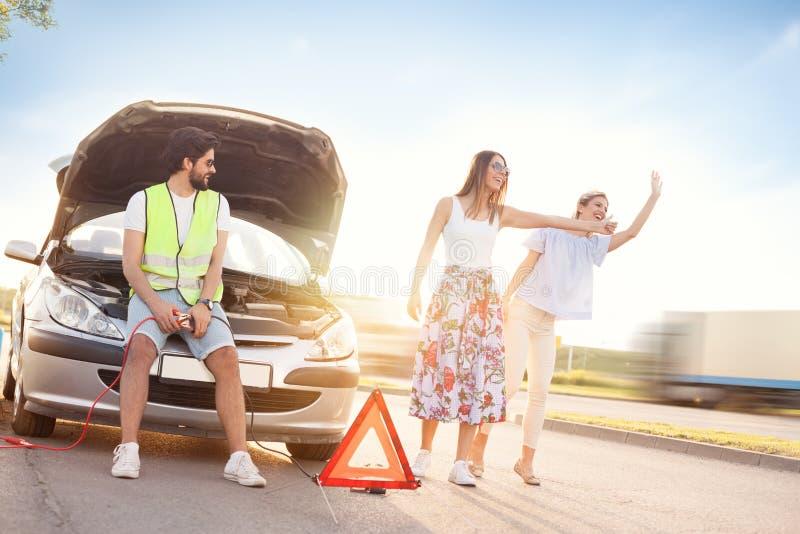 Mężczyzna obok łamanego samochodu opuszcza jego przyjaciół hitchhiking dla obraz royalty free