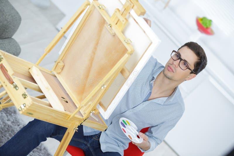 Mężczyzna obraz na canva w domu zdjęcie royalty free
