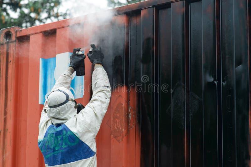 Mężczyzna obraz z graffiti aerosolu puszką, outdoors Proces pai zdjęcia stock