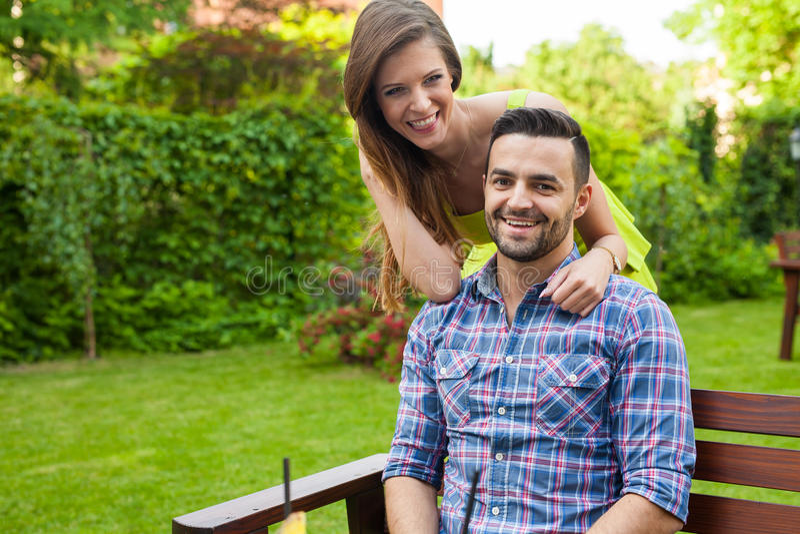 Mężczyzna obsiadanie na ławce w ogródzie Dziewczyny pozycja za on P zdjęcia stock