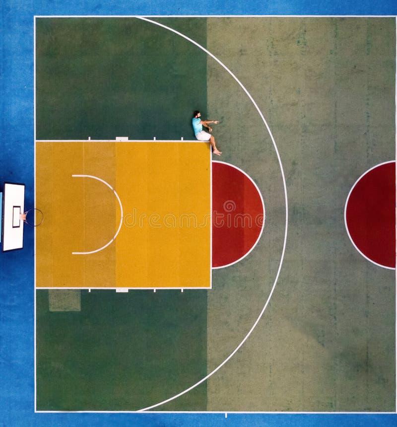 Mężczyzna obsiadanie na boisko do koszykówki zdjęcia stock