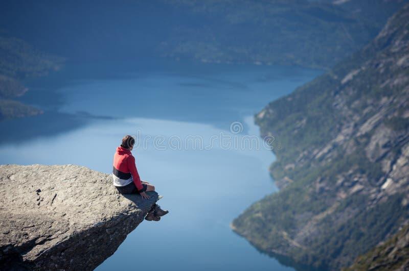 Mężczyzna obsiadanie na trolltunga skale w Norway fotografia stock