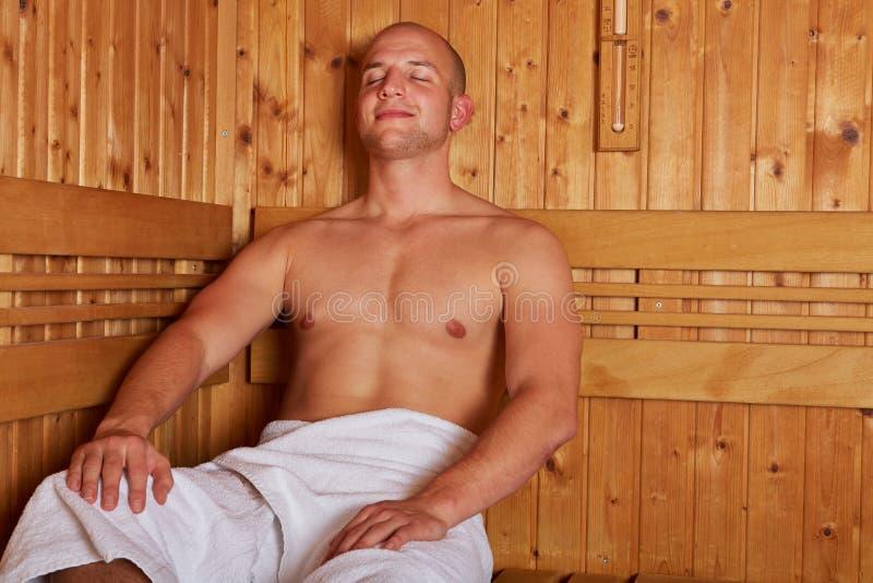 Mężczyzna obsiadanie relaksujący w parowym sauna zdjęcia stock