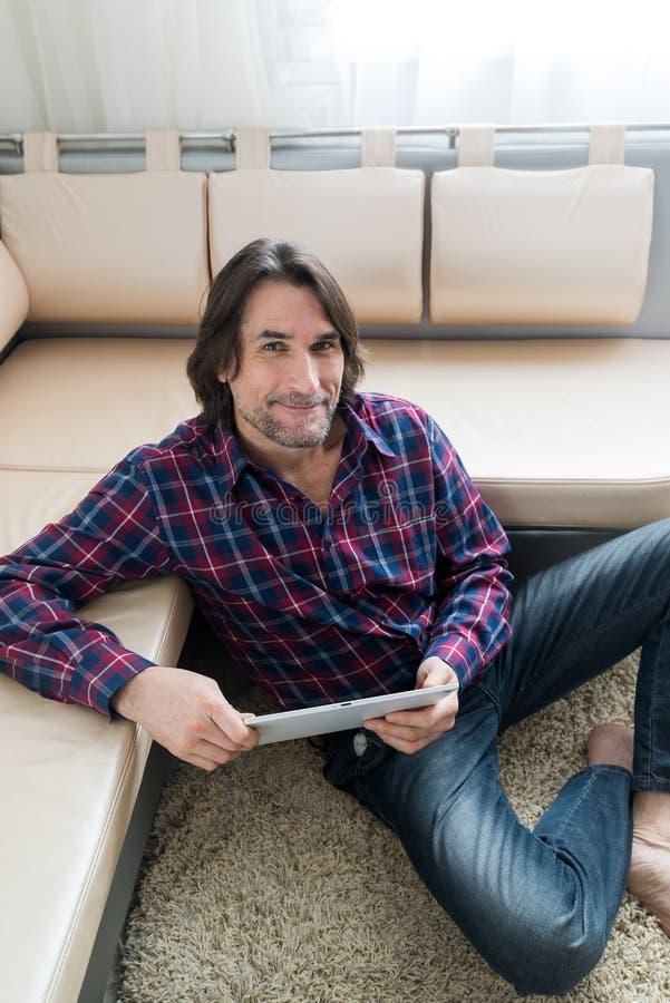 Mężczyzna obsiadanie w kanapie używać elektroniczną pastylkę zdjęcie stock
