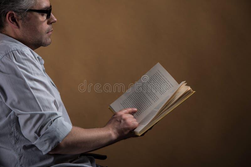 Mężczyzna obsiadanie w krześle i czytelniczej książce obrazy royalty free