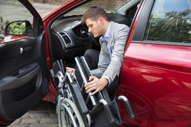Mężczyzna obsiadanie W samochodzie Składa Jego wózek inwalidzkiego fotografia royalty free