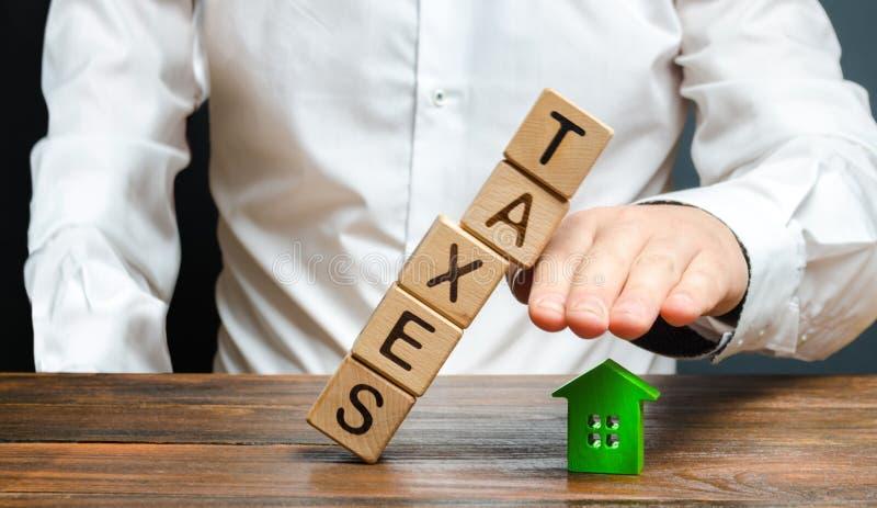 Mężczyzna ochrania jego rękę z figurką dom od spada wierza sześciany z słowo podatkami Ciężki obciążenie podatkowe, ochrania obraz stock
