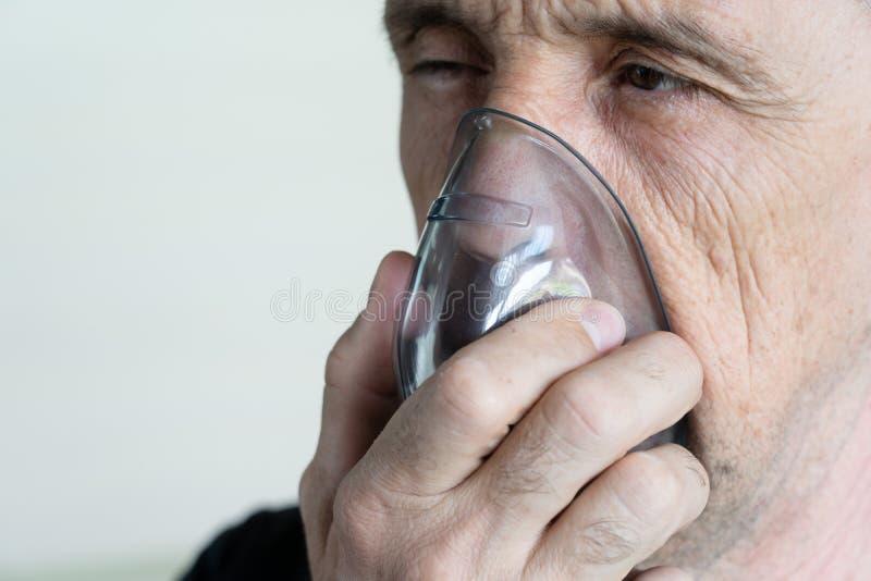 Mężczyzna oddycha tlen przy użyciu maski Zbliżenie starego mężczyzny wdychającego fotografia stock