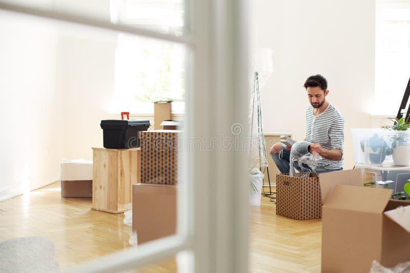 Mężczyzna odpakowania materiał od pudełek podczas gdy meblujący nowego mieszkanie po r fotografia stock