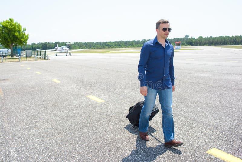 Mężczyzna odprowadzenie przy lotniskową ciągnięcie walizką zdjęcia stock