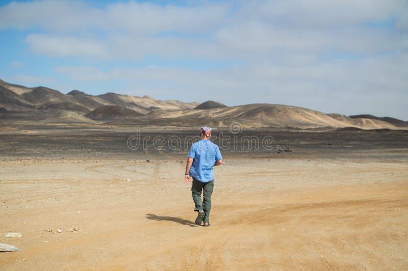 Mężczyzna odprowadzenie w Pustynnym krajobrazie z górami w Namibia obraz stock