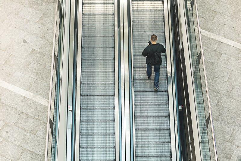 Mężczyzna odprowadzenie wokoło patrzeć jego telefon komórkowego Mężczyzna wspina się eskalator zdjęcie royalty free