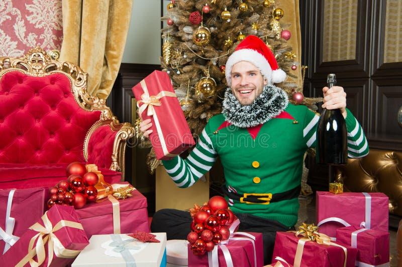 Mężczyzna odzieży Santa elfa kapeluszowi ubrania świętują boże narodzenia wnętrze dekorujący jedlinowy drzewo i prezenty Bożenaro fotografia royalty free